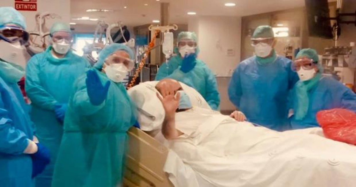 Un home en una llitera envoltat d'infermers amb EPI