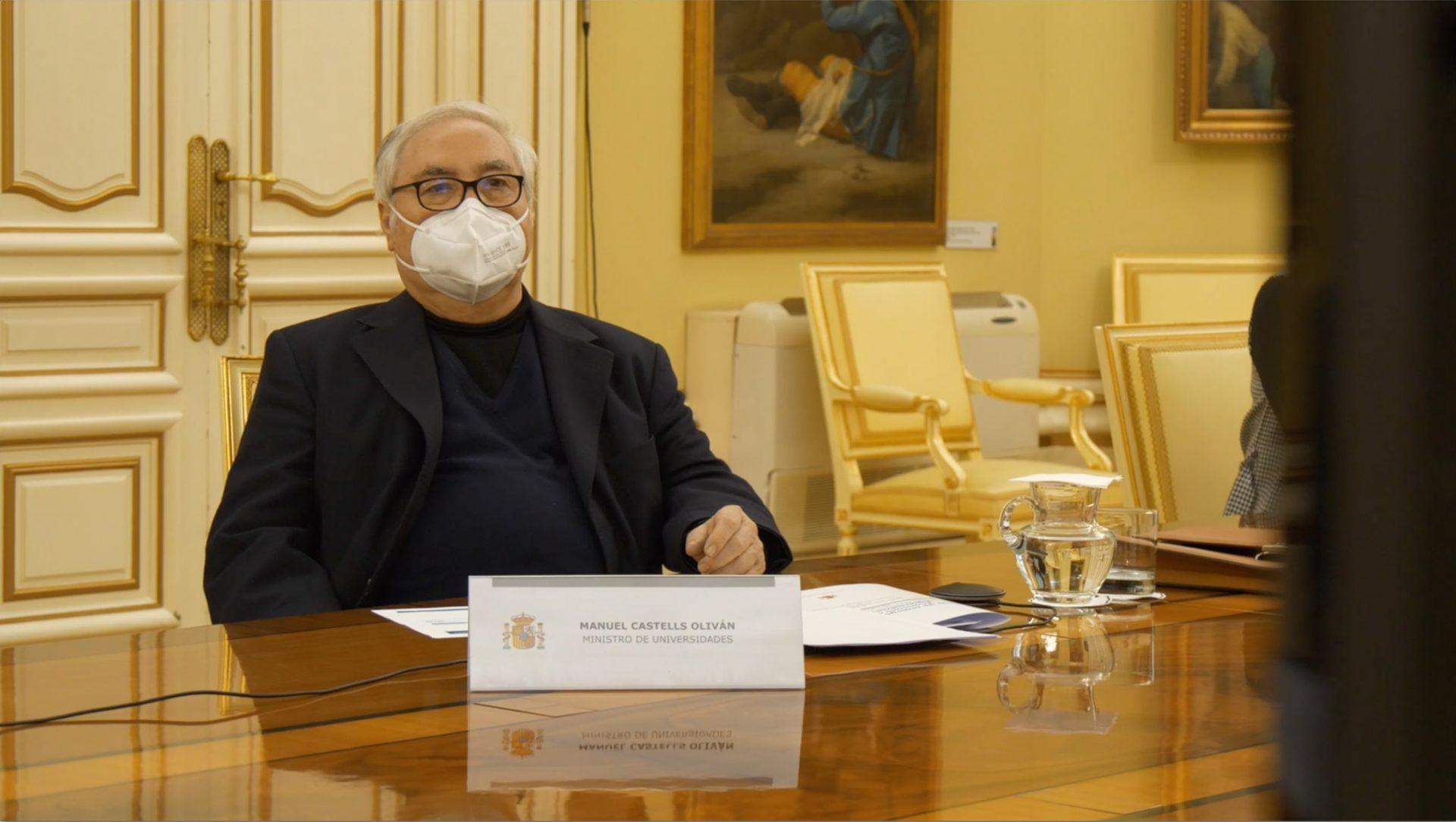 Manuel Castellos sobre una taula després d'un cartell amb el seu nom