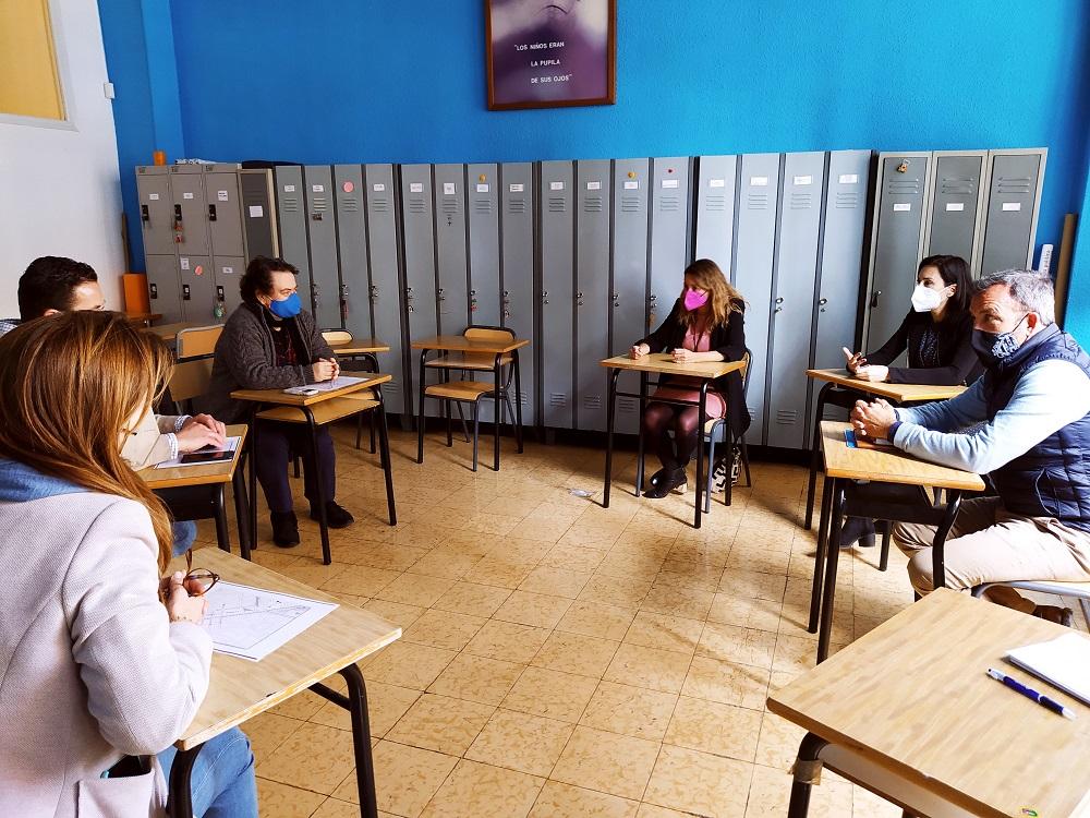 imagen de personas adultas, alguns políticos del PP de Castellón, dentro de un aula con mesas dispuestas en circulo y separadas