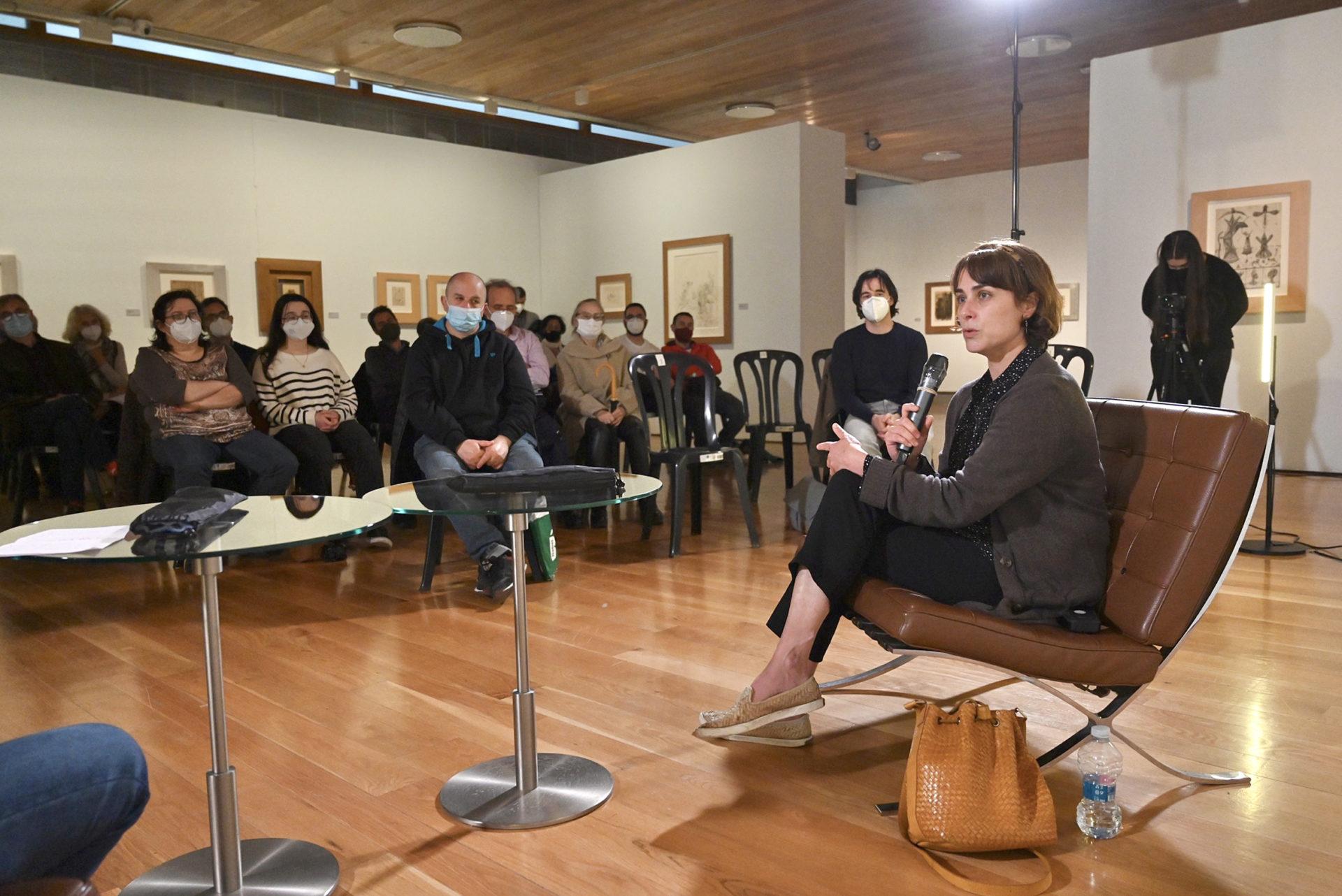 Una mujer habla ante un público en un aforo pequeño