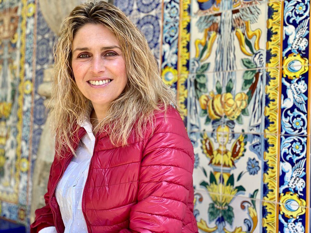 Primer Plano de Marta Barrachina sonriente, con cazadora roja sobre un fondo de azulejos con motivos típicos de la cerámica de la provincia