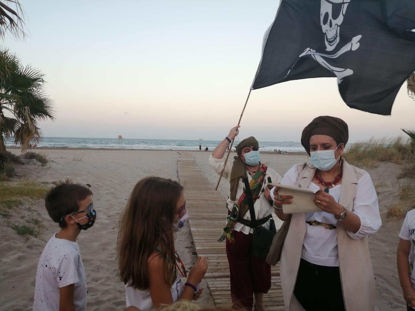 Dos personas vestidas de piratas teen una carta y enarbolan unabandera pirata en un paisaje de playa con dos niños mirando