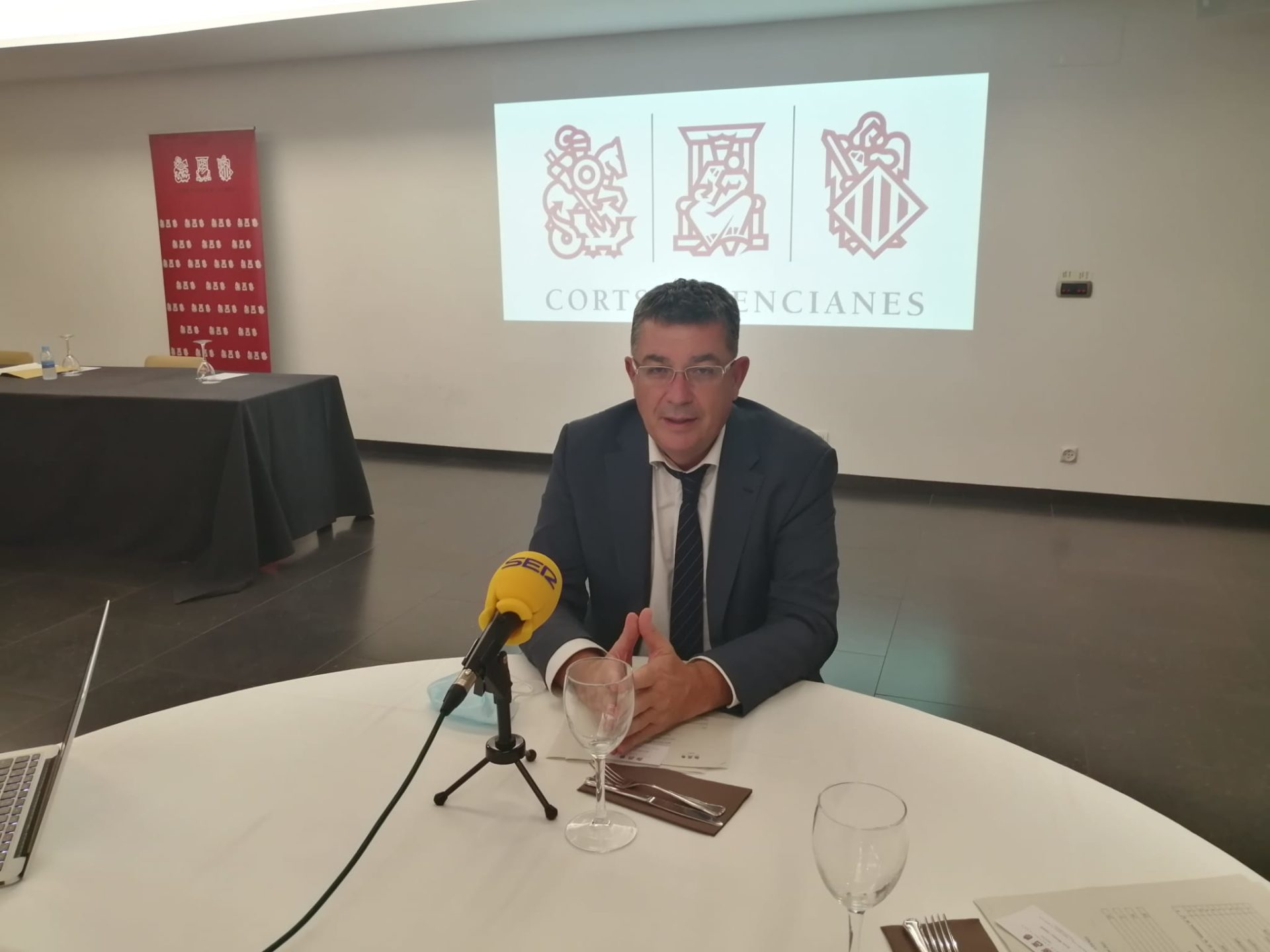 Imagen del president de les Corts Valencianes sentado con una ppantalal de proyección con el logotipo de los Corts tres él